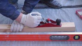 El carpintero principal monta el piso de madera de pino - suelo respetuoso del medio ambiente retraso que atornilla al hormig?n almacen de video