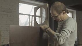 El carpintero profesional conecta a dos diversos tableros de madera en la tabla ensamblaje almacen de video