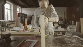 El carpintero profesional conecta a dos tableros pulidos de madera muebles ensamblaje almacen de metraje de vídeo
