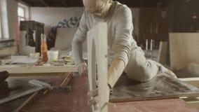 El carpintero profesional conecta el tablero pulido de madera dos por el martillo ensamblaje almacen de video