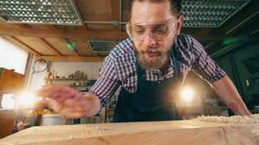 El carpintero profesional trabaja en una tienda, quitando virutas de una tabla almacen de video