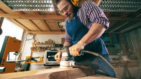 El carpintero profesional utiliza la máquina que enarena, trabajando con madera en un taller almacen de metraje de vídeo