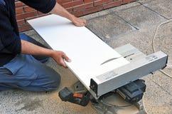 El carpintero que cortaba un tablero de melamina blanca con poder del disco vio Imagenes de archivo