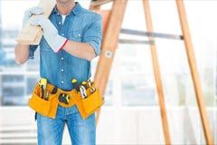 El carpintero que lleva una correa y una bata de la herramienta está llevando a cabo a un tablero de madera contra fondo de la es Foto de archivo