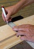 El carpintero que sostiene un cartabón y dibuja una línea imágenes de archivo libres de regalías