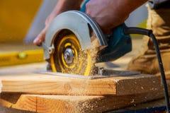 El carpintero que usaba la circular vio para cortar a los tableros de madera con las herramientas eléctricas de la mano imagen de archivo