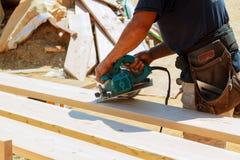 El carpintero que usaba la circular vio para cortar a los tableros de madera Detalles de la construcción del trabajador de sexo m Imagenes de archivo