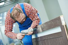 El carpintero trabaja con el taladro fotografía de archivo libre de regalías