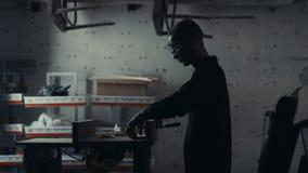 El carpintero trabaja con un rompecabezas eléctrico y productos de madera de los procesos Imagen de archivo libre de regalías