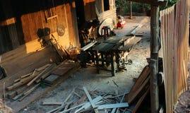 El carpintero vio la madera al lado de la sierra del poder en casa Imagen de archivo libre de regalías