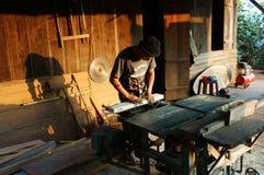 El carpintero vio la madera al lado de la sierra del poder en casa Foto de archivo libre de regalías