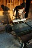 El carpintero vio la madera al lado de la sierra del poder en casa Imágenes de archivo libres de regalías