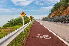 El carril rojo para la bicicleta en el camino entre la playa y la montaña imagen de archivo