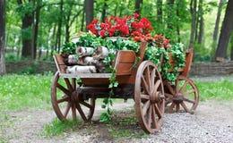 El carro con el geranio rojo del escarlata florece en parque Foto de archivo libre de regalías