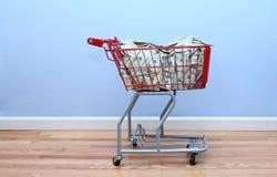 El carro de compras rojo llenó del dinero Fotos de archivo