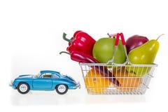 El carro de la compra con los ultramarinos tirados por imagen del concepto del coche está por completo Foto de archivo libre de regalías