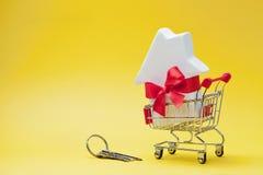 El carro de la compra con la pequeña casa blanca adornó la cinta del arco y el manojo de llaves rojos en fondo amarillo Compra de Imagen de archivo