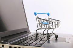 El carro de la compra est? en el ordenador port?til Concepto en l?nea de las ventas imagen de archivo libre de regalías