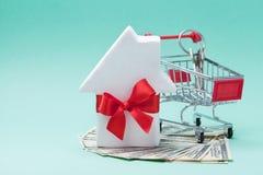 El carro de la compra miniatura, pequeña casa blanca adornó la cinta roja del arco, dólares de dinero y llavero Compra de un nuev Imagenes de archivo