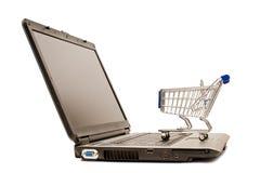 El carro de la compra miniatura se sienta en una computadora portátil para XXXL que hace compras en línea Fotografía de archivo libre de regalías
