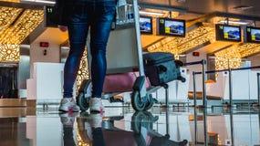 El carro del pasajero y del equipaje delante del escritorio del contador de enregistramiento Imagen de archivo libre de regalías