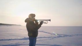 El carro enfoca en tiro del músico caucásico en el perfil que acaba tocando la trompeta en fondo de la naturaleza del invierno almacen de video