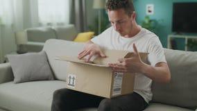 El carro fuera del hombre joven abre un paquete de la cartulina en el sof? en su sala de estar metrajes