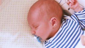 El carro hermoso del retrato del primer del bebé el dormir tiró de la mano en una profundidad baja de la cara recién nacida del b metrajes