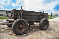 El carro roto abandonado viejo está en un campo verde del otoño en el campo foto de archivo