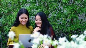 El carro tiró de adolescente asiático lindo con el ordenador portátil en el jardín Imagen de archivo