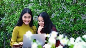 El carro tiró de adolescente asiático lindo con el ordenador portátil en el jardín Foto de archivo