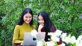 El carro tiró de adolescente asiático lindo con el ordenador portátil en el jardín Imagenes de archivo