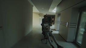 El carro tiró de dos hombres de negocios locos que montaban la silla de la oficina y que lanzaban los papeles para arriba mientra