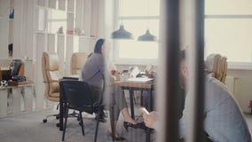 El carro tiró de la reunión de negocios multiétnica en oficina moderna Hombre de negocios europeo acertado joven usando el smartp metrajes