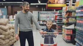 El carro tiró de padre joven y del hijo de la familia que caminaban a través de tienda de alimentación con la carretilla que mira almacen de metraje de vídeo