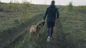 El carro tiró del hombre deportivo joven que corría con su perro del bullmastiff al aire libre en el parque y que preparaba su an almacen de metraje de vídeo