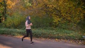 El carro tiró, funcionando con a la muchacha musulmán joven en hijab en bosque otoñal almacen de metraje de vídeo