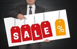 El cartel de las etiquetas de la venta es sostenido por el hombre de negocios Fotografía de archivo