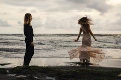 El casarse lovestory, apenas pareja casada cerca del océano en la puesta del sol Imagenes de archivo
