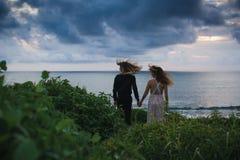 El casarse lovestory, apenas pareja casada cerca del océano en la puesta del sol Fotografía de archivo