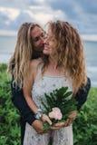 El casarse lovestory, apenas pareja casada cerca del océano en la puesta del sol foto de archivo libre de regalías