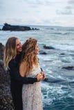 El casarse lovestory, apenas pareja casada cerca del océano en la puesta del sol foto de archivo