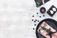 El casarse o ajuste festivo de la tabla Placas, velas y cubiertos con la materia textil decorativa en fondo de madera Imagenes de archivo