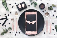 El casarse o ajuste festivo de la tabla Placas, velas y cubiertos con la materia textil decorativa en fondo de madera Foto de archivo