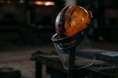 El casco anaranjado viejo de la construcción en una fábrica, puso un palillo imagenes de archivo