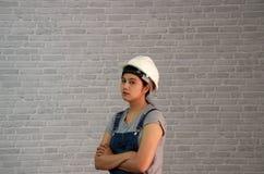 El casco blanco de las mercancías de la mujer del técnico con el delantal gris de los vaqueros de la camiseta y del dril de algod foto de archivo libre de regalías