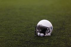 El casco blanco protector para el juego del rugbi del fútbol americano miente en la hierba verde en el campo de deportes foto de archivo