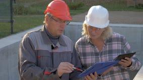 El casco de And Client In del constructor discute la construcción según proyecto del plan almacen de metraje de vídeo