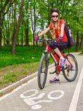 El casco de la bicicleta de la muchacha y el camino del ciclyng de la mochila que llevan montan en bicicleta Imagenes de archivo