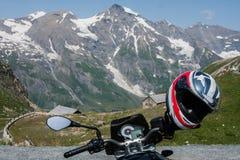 El casco de la motocicleta colgó en el manillar, alto Al de Grossglockner Imagen de archivo libre de regalías